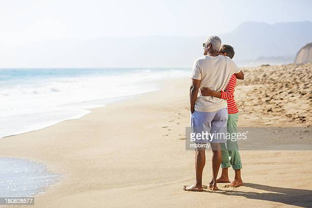 Senior African American couple embracing on beach