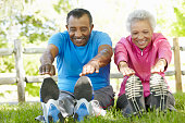 Senior African American Couple Exercising In Park Stretching To Touch Toes
