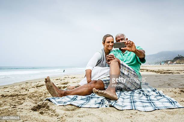 Senior African American couple having fun with smartphone on beach