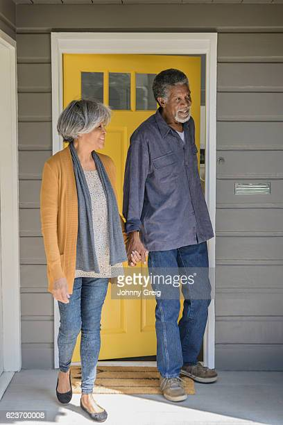 Senior African American couple leaving house and closing door