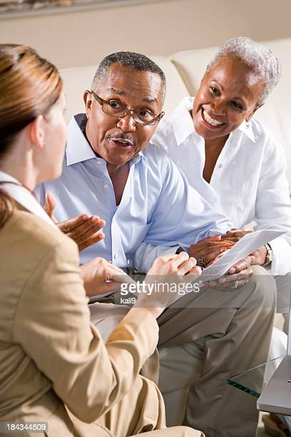 Senior African American couple meeting with female financial adv