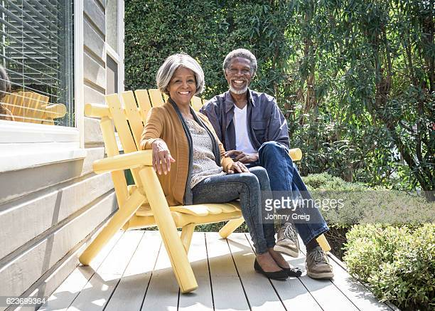 Senior African American couple on bench, smiling towards camera