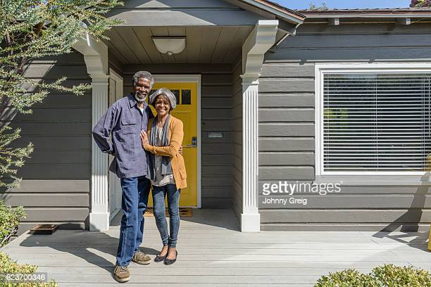 Senior African American couple smiling outside their home