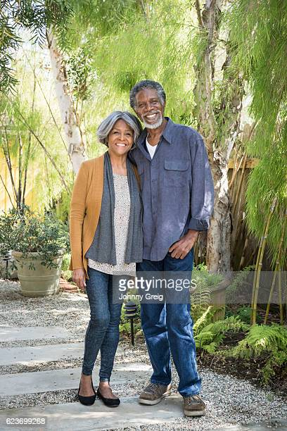 Senior African American couple standing on garden path, smiling