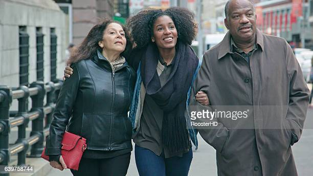 Senior African American Couple Walk with their Adult Daughter