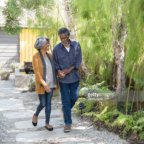 Senior African American couple walking on garden path