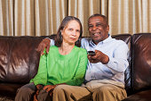 Senior African American couple (60s) sitting together side by side on couch with remote control, watching TV.  Man has his arm around woman resting his hand comfortably on her shoulder, holding remote