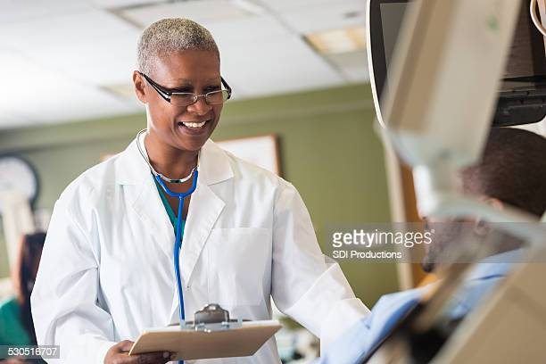 Senior African American female doctor comforting patient in hospital