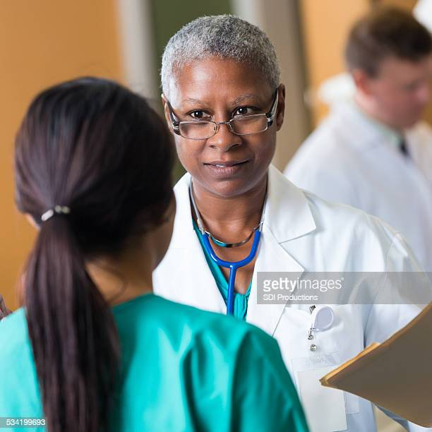 Senior African American female doctor talking with nurse in hospital