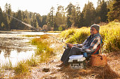Senior African American Man Fishing By Lake