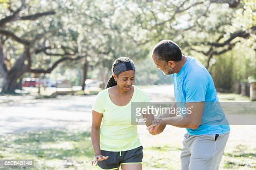 Senior African American man helping woman walk slowly : Stockfoto