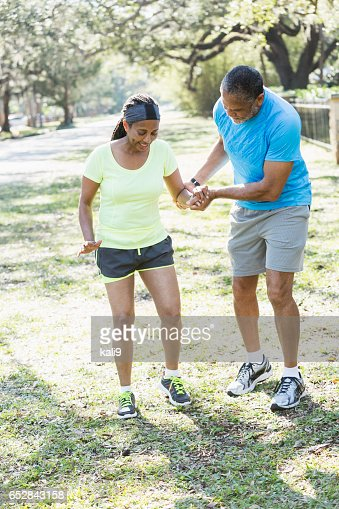 Senior African American man helping woman walk slowly : Stock Photo