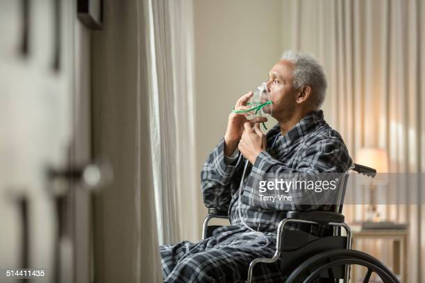 Senior African American man in wheelchair breathing with mask