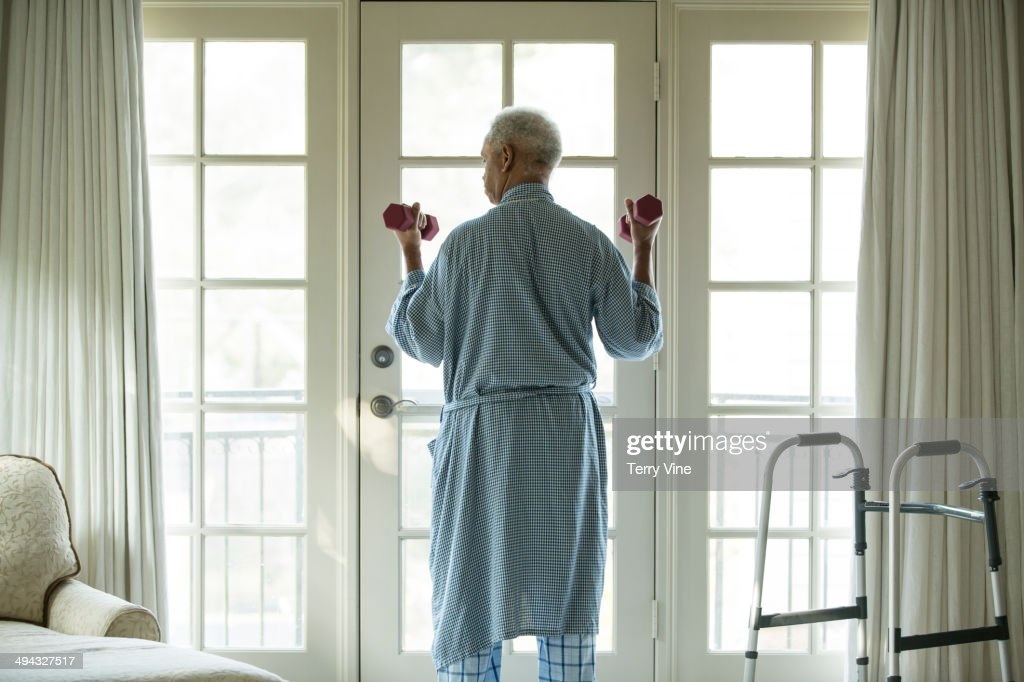 Senior African American man lifting weights at home