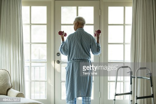 Senior African American man lifting weights at home