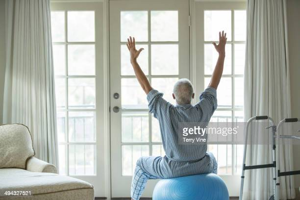 Senior African American man on fitness ball at home