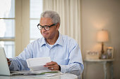 Senior African American man paying bills
