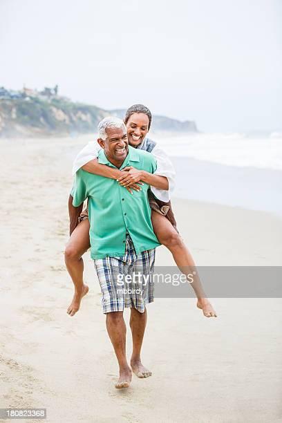 Senior African American man piggybacking his wife at beach
