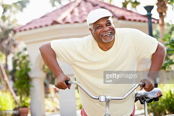 Senior African American man riding bicycle
