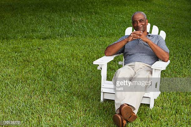 Senior African American man sitting in adirondack chair