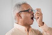 Senior African American man using asthma inhaler