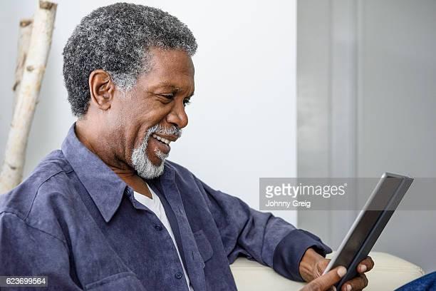 Senior African American man using digital tablet, smiling