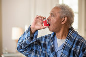 Senior African American man using inhaler