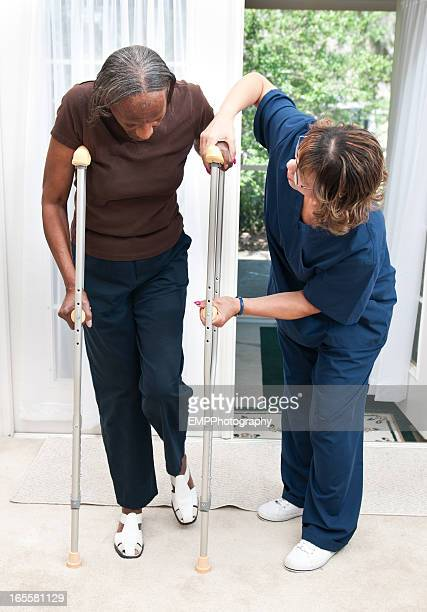 Senior African American Woman getting help with Crutches