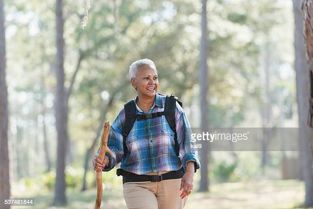 Senior African American woman hiking through woods