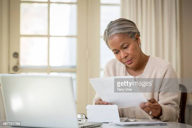 Senior African American woman paying bills