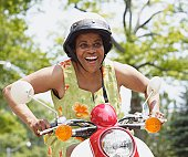 Senior African American woman riding motor scooter