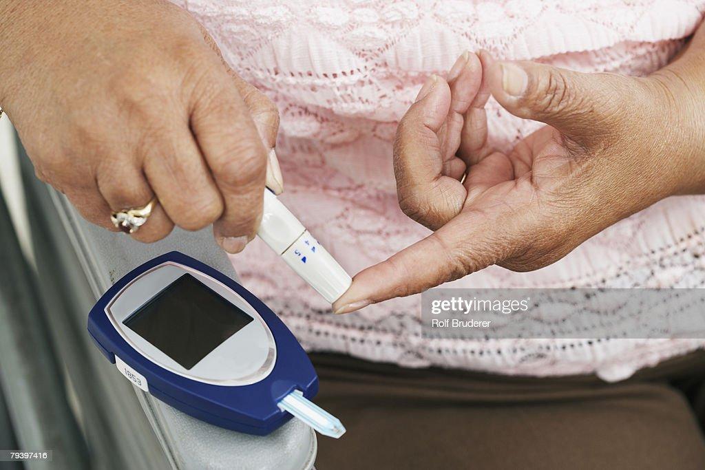 Senior African American woman testing blood sugar : Stock Photo