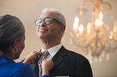 Senior African American woman tying husband's tie