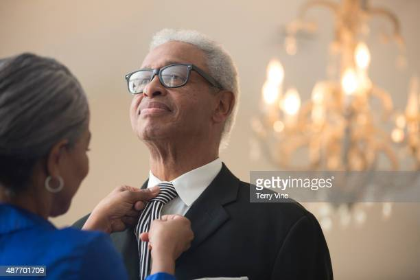 Senior African American woman tying husband's tie