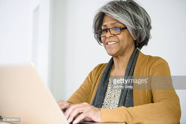 Senior African American woman using laptop, wearing glasses