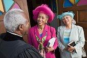 Senior African American women talking to Reverend