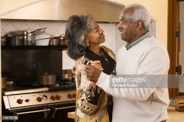 Senior African couple dancing in kitchen