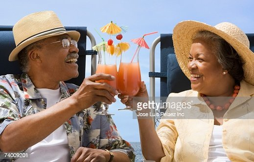 Senior African couple toasting with tropical cocktails : Stock Photo