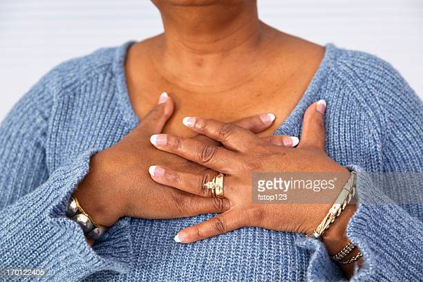Senior African descent woman clutches chest in pain