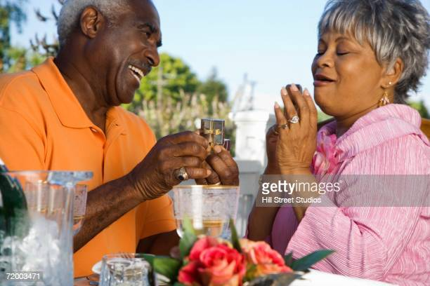 Senior African man giving senior African woman gift