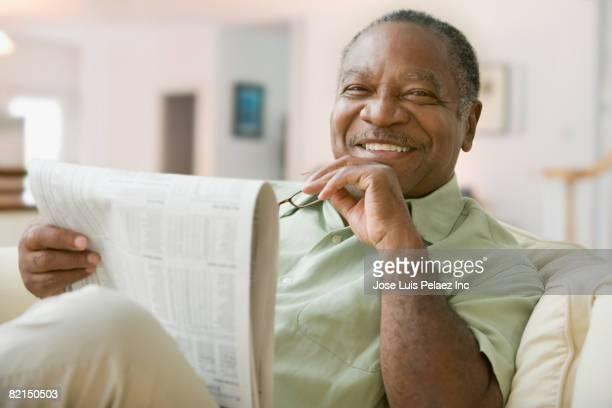 Senior African man holding newspaper