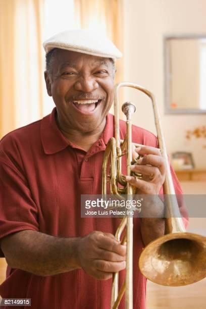 Senior African man holding trombone