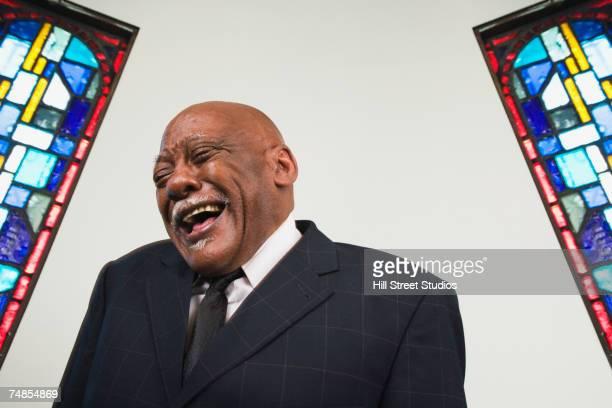 Senior African man laughing in church