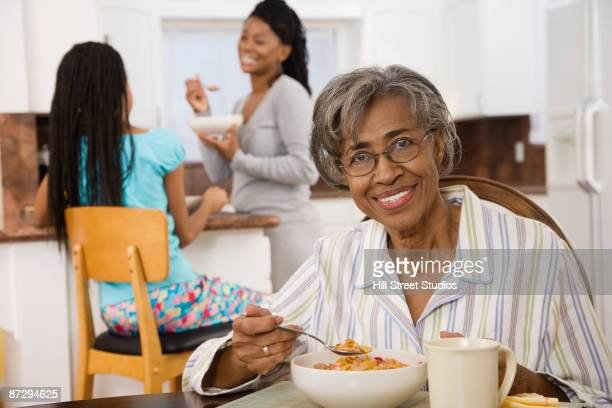 Senior African woman eating breakfast in kitchen