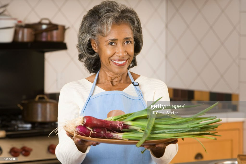 Senior African woman holding plate of vegetables : Stock Photo