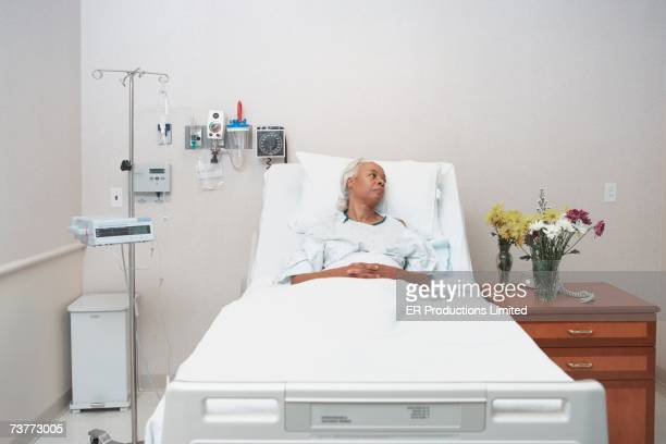 Senior African woman laying in hospital bed