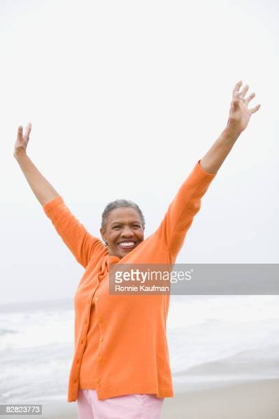 Senior African woman stretching on beach