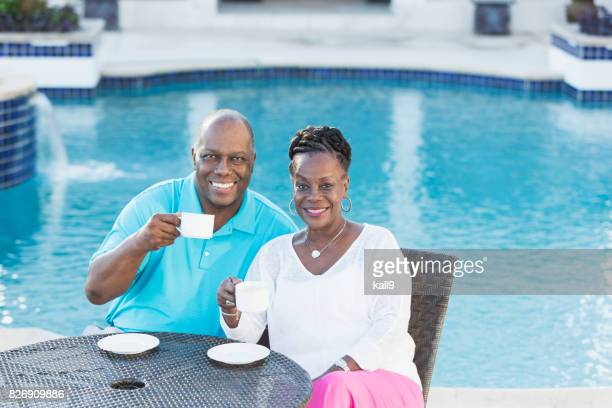 Senior African-American couple by pool drinking coffee