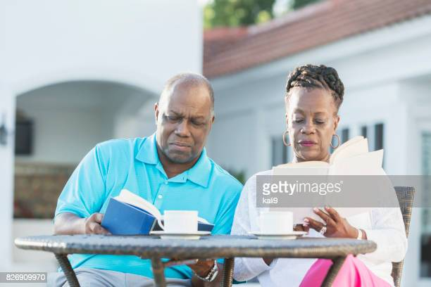 Senior African-American couple on patio, reading