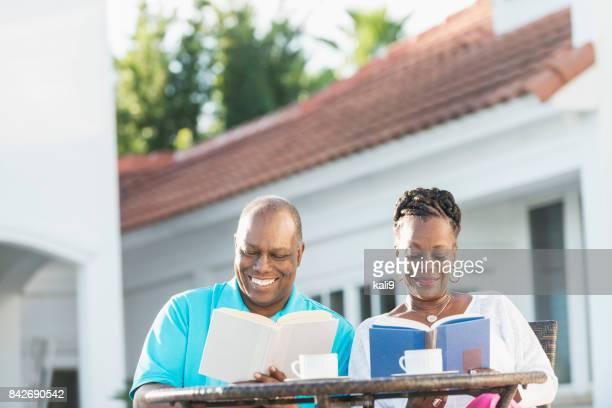 Senior African-American couple on patio, reading